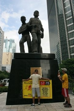coach joar putting the iamninoy runners' banner at the Ninoy Aquino monument